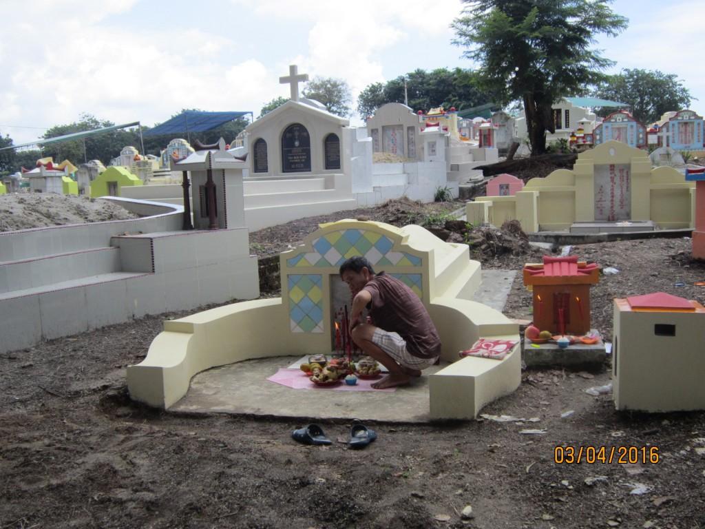 Pak Ali sedang menata sesembahan di makam nenek buyutnya